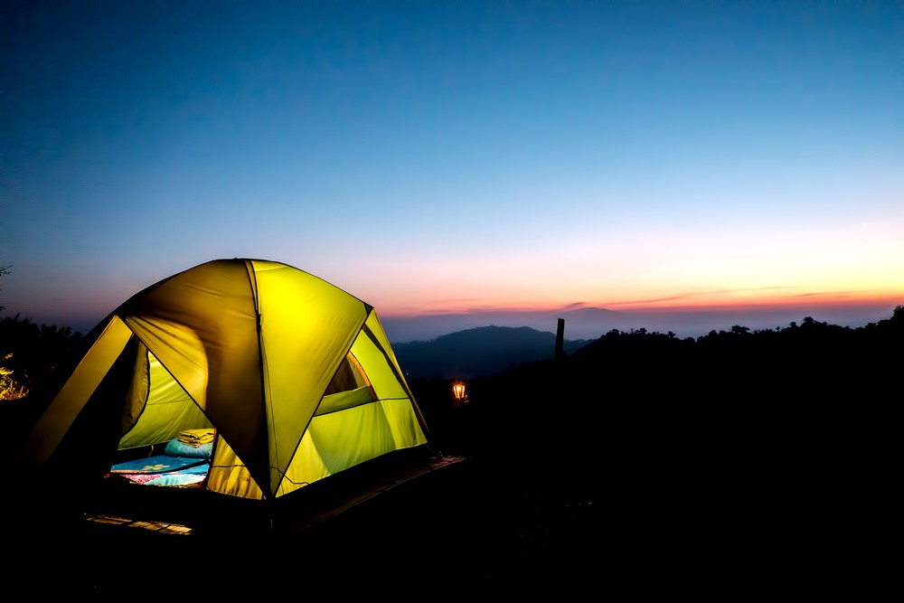 sunset over tent with camping lights