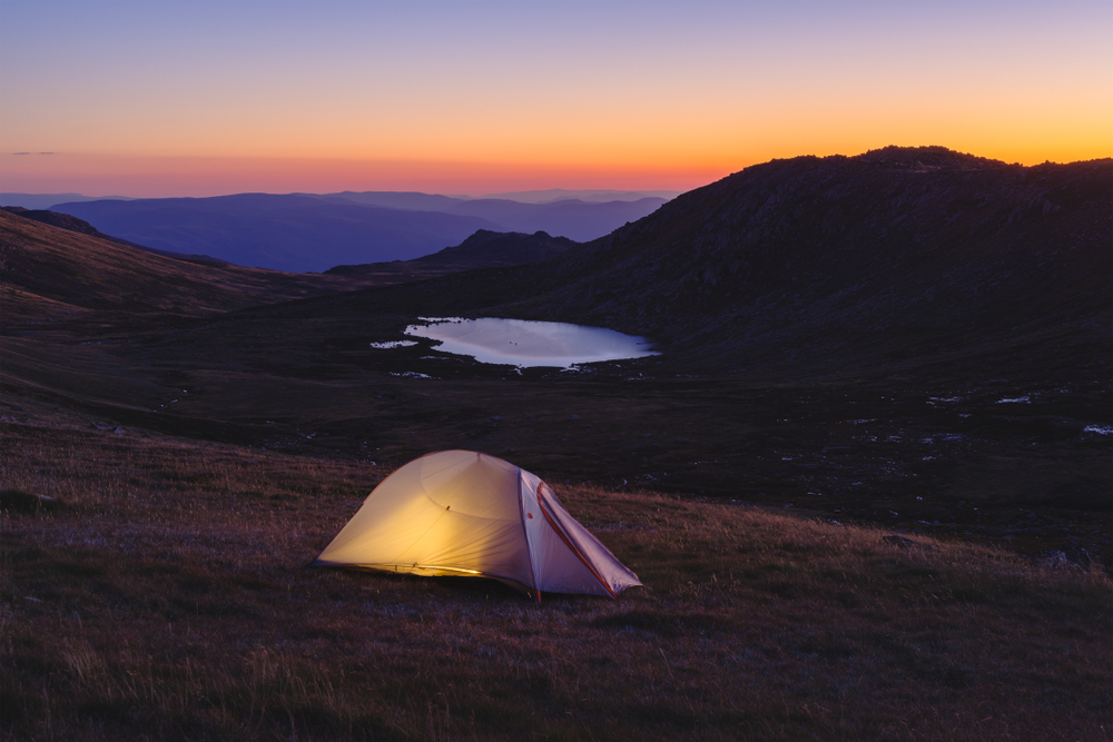 camping tent set up on hillside at sunset